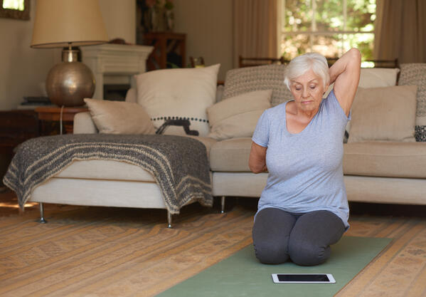 Elderly woman exercising at home with telehealth tablet