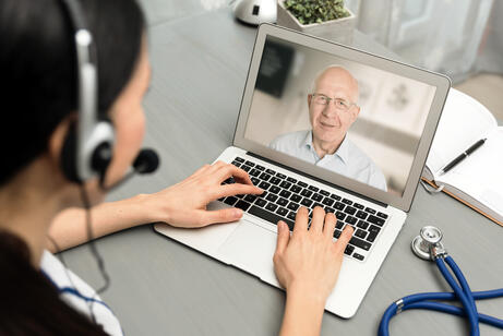 Doctor talking with senior patient via virtual visit