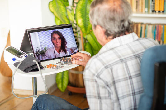 Elderly man with blood pressure cuff and medications using telehealth