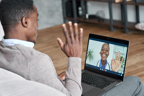 Doctor and patient waving during virtual visit